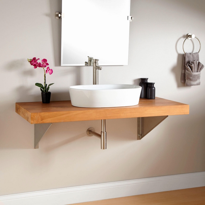 minimalistic white sink, with a shiny metal faucet, on a wooden counter, near a mirror, mounted on a beige wall, small bathroom decoration ideas, pink potted orchid, and a grey towel, on a metal ring
