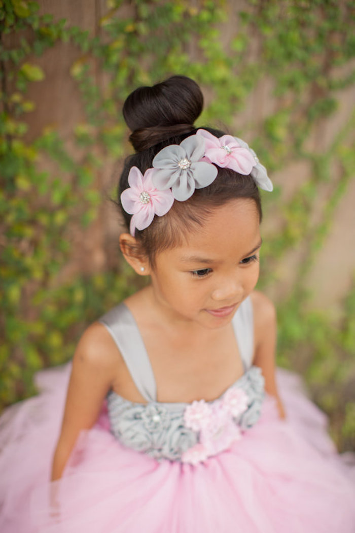 topknot worn by a small girl, in a formal pale grey, and powder pink dress, little girl hairstyles, matching floral headband