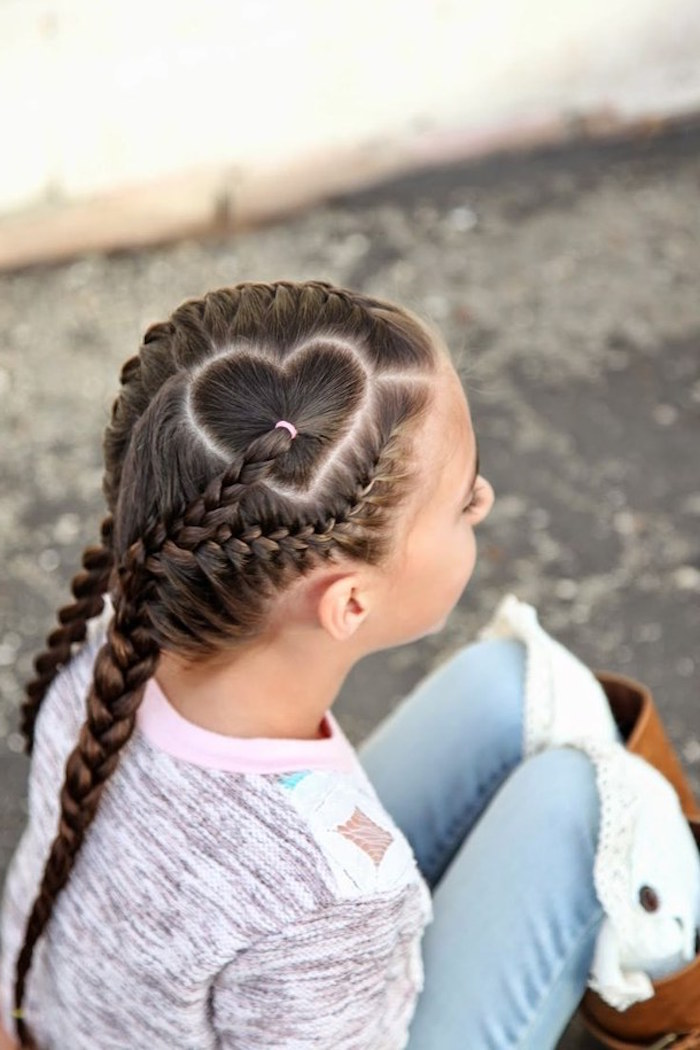 sitting young girl, dressed in pale jeans, and a multicolored jumper, with dark brunette hair, woven into several braids, kids hairstyles, forming a heart pattern on top of her head