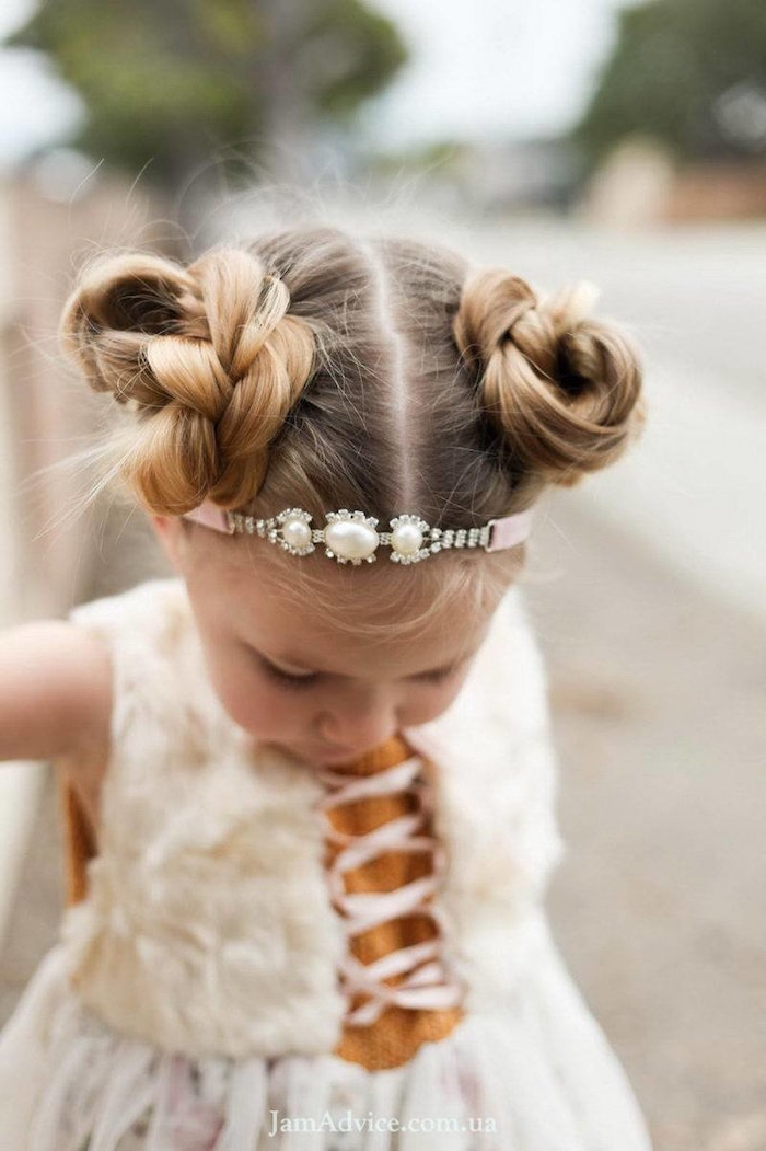 headband in pink, decorated with diamante, and pearl-like stones, on the head of a small blonde child, with two braided buns, little girl haircuts
