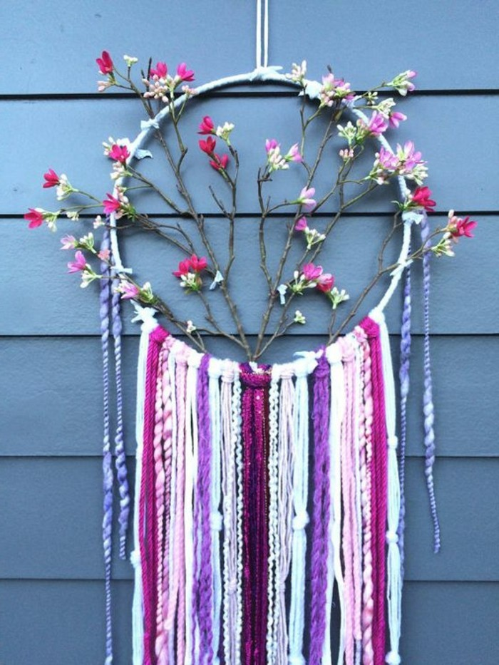 branches with faux pink, and white blossoms, decorating a dreamcatcher, with purple and maroon, white and pink tassels, big dream catchers, hung near a blue surface
