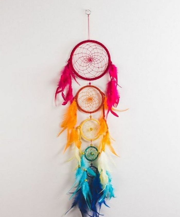 red and orange, yellow and turquoise, and dark blue, dream catcher nets, decorated with feathers in corresponding colors, and attached to one another, big dream catchers, on an off-white wall