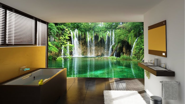 photo wallpaper with a greenish blue lake, and several waterfalls, decorating one of the walls of a room, with a white and brown bathtub, and matching brown sinks, modern bathroom ideas, brown tiled floor, and a yellow accent wall