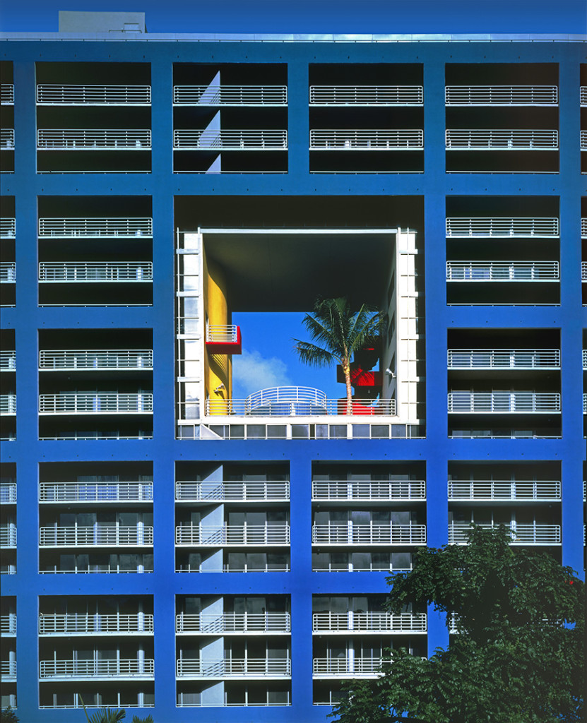 blue rectangular building, with a hollow square in the middle, containing elements in yellow, red and white, and a palm tree, atlantis condominium, postmodern architecture, lots of terraces with white railings