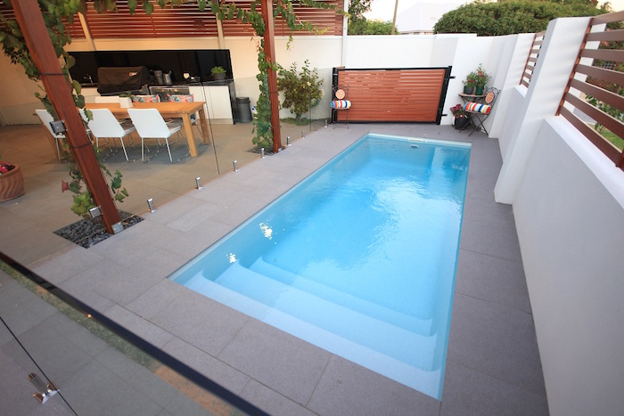 table with six chairs, near a blue rectangular pool, surrounded by grey tiles, small inground pools, with a glass fence