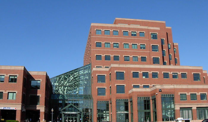 structure with rectangular shape, with multilayered effect, made from red and pale beige bricks, postmodernism examples, large glass details and many windows