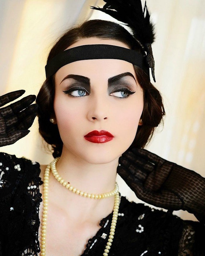 feather in black, decorating the black headband, of a woman with 1920s flapper make up, painted eyebrows and smoky eyes, bright red lipstick