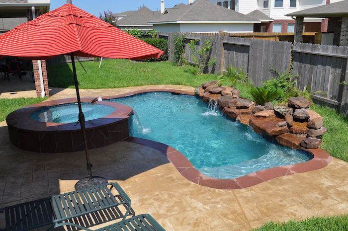 umbrella in red, near two metal sun beds, in a garden, containing a pool, decorated with stones