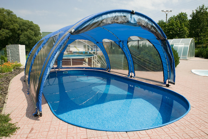cover for a pool, made from clear, blue and black plastic, over a blue oval pool, small inground swimming pools, surrounded by beige tiles