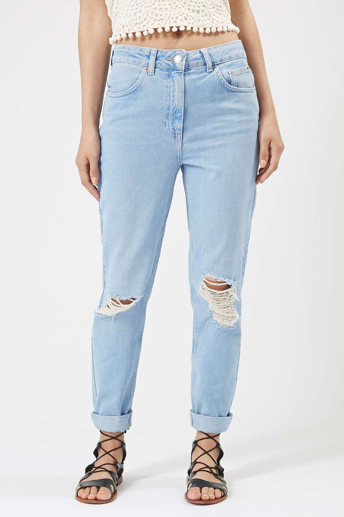 rolled-up pale blue jeans, with rips near the knees, 90s themed outfits, worn with lace up gladiator sandals, and a cropped lacy cream top