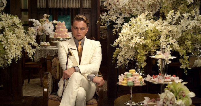 great gatsby outfits, leonardo di caprio as jay gatsby, dressed in a white suit, brown vest and grey shirt, yellow tie and holding a cane