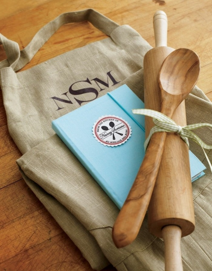 light blue recipe book, under a wooden rolling pin, and a wooden spoon, tied together with a ribbon, creative gift ideas, large burlap bag