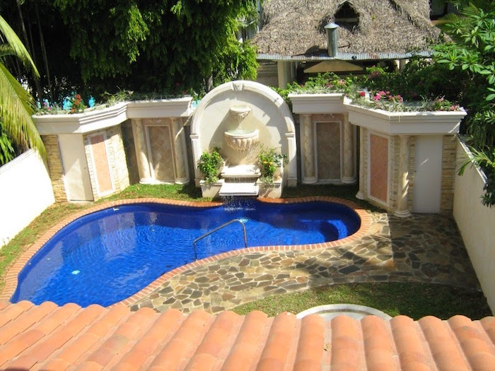 wall with columns and plaster details, decorated in ancient roman style, near a blue pool, in a small garden, small inground swimming pools, stone covered floor