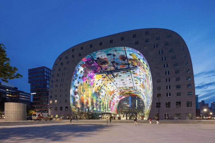 light projections in different colors, inside the hollow area of a building, with rounded edges, and many square windows, post modernity, a square with people