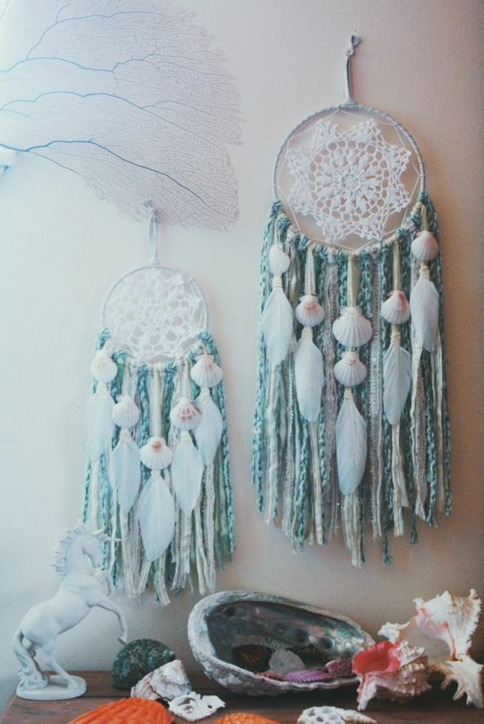 unicorn figurine in white, near two dream catchers, with white crochet doilies, teal blue tassels, white feathers and seashells