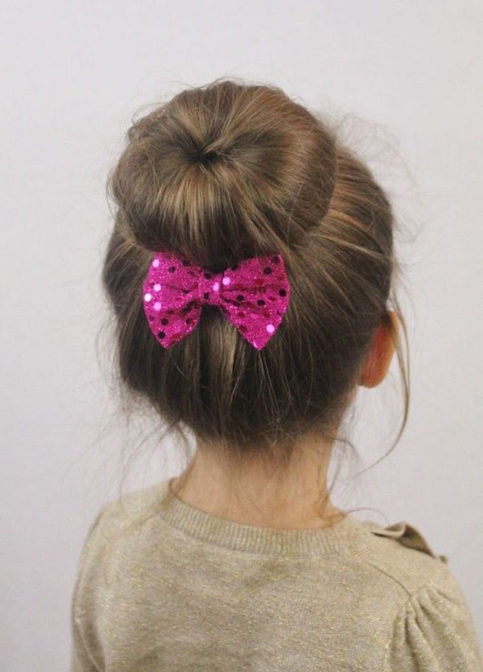 donut bun with a sparkly, sequined fuchsia pink bow, on the brunette head of a child, simple hairstyles