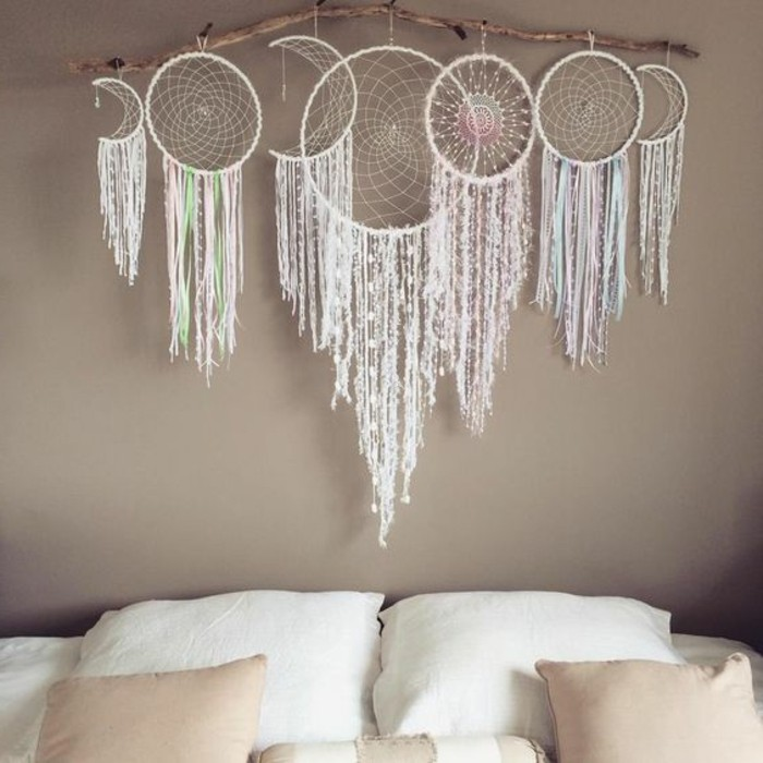 wall decoration with seven dreamcatchers, four round and three crescent shaped, hanging from a large dried branch, big dream catchers, above a bed