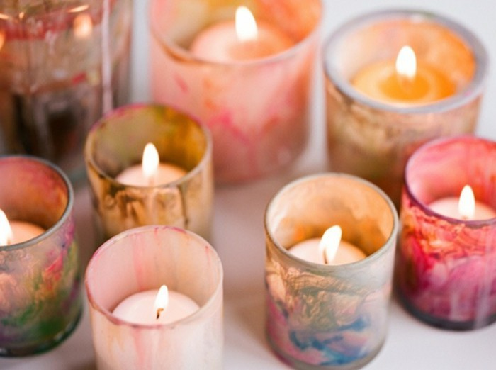 shot glasses, decorated with multicolored splashes of paint, containing small lit candles, cute birthday ideas, on a white surface