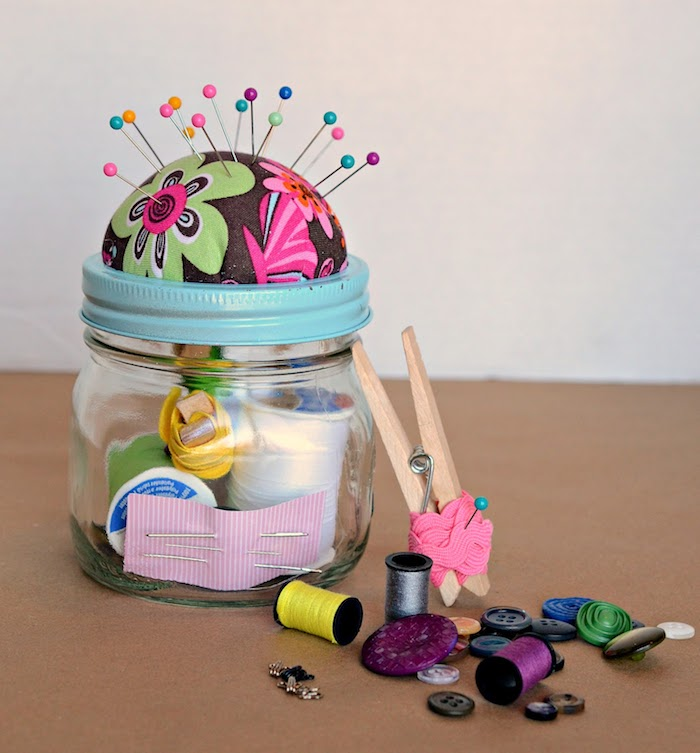 sewing station inside a glass jar with blue lid, diy christmas gifts for boyfriend, buttons yarn and needles, on a brown surface