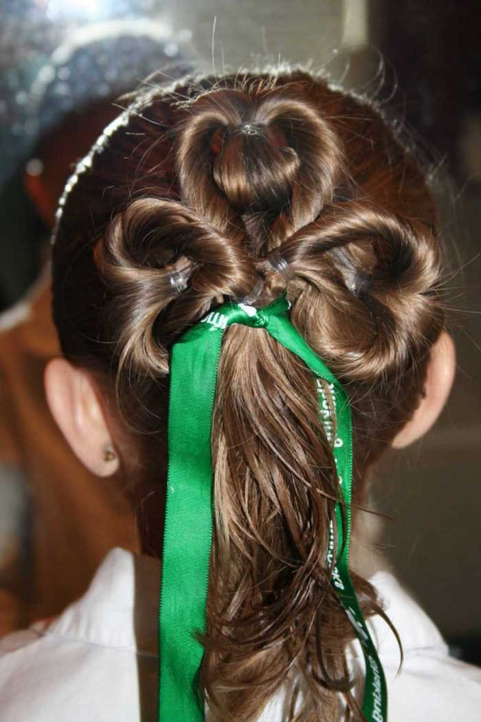clover-like hair braid, decorated with a green ribbon, on the brunette head of a young girl, st. patrick's day little girl haircuts, shamrock motif