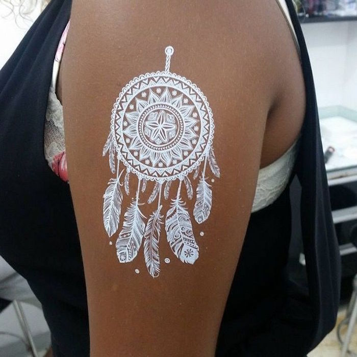 brown arm adorned with a white, detailed temporary tattoo, cute henna designs, in the shape of a dreamcatcher