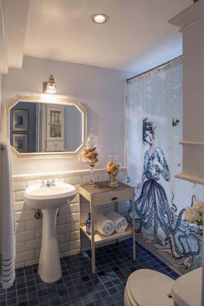 graphic print, of an octopus mermaid, on a shower curtain, in a bathroom with pale walls, decorated with white subway tiles, small bathroom decoration ideas, shabby chic cabinets, and two glass containers, filled with seashells
