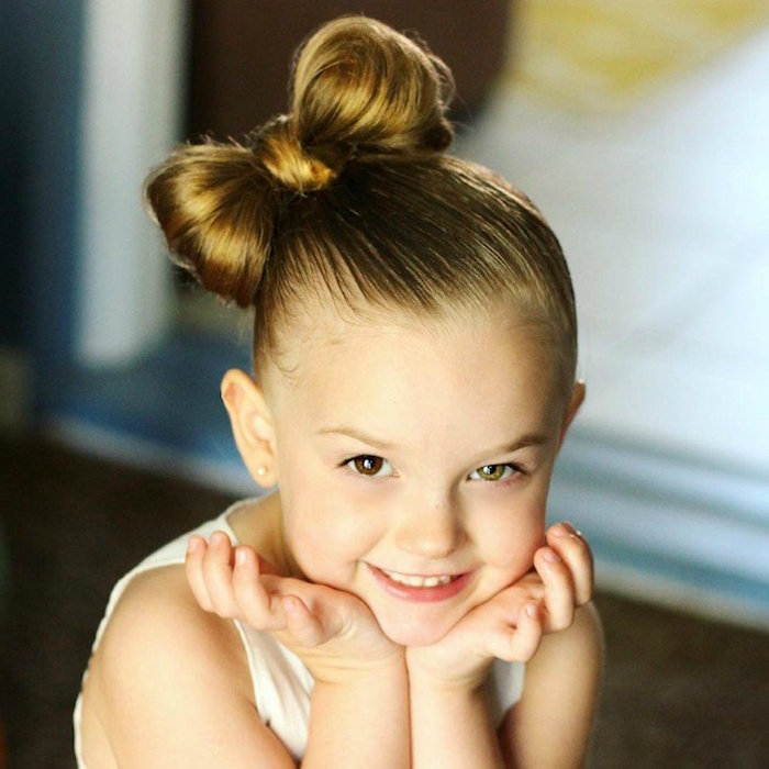 bow-shaped braid, on the side of a child's head, little girl haircuts, one of the child's eyes is brown, and the other green