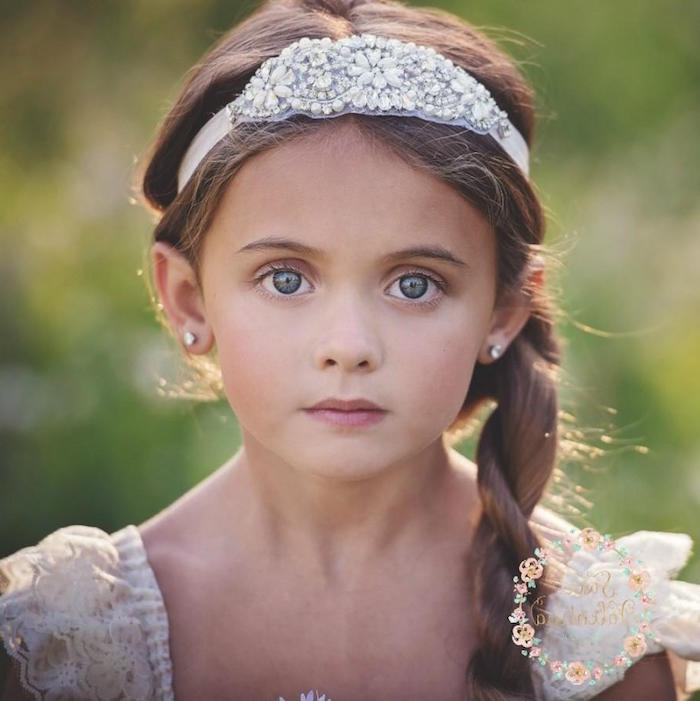 bejeweled white headband, with pearl-like details, on the head of a young child, with brunette hair, tied into a side braid, falling over her shoulder, cute hairstyles