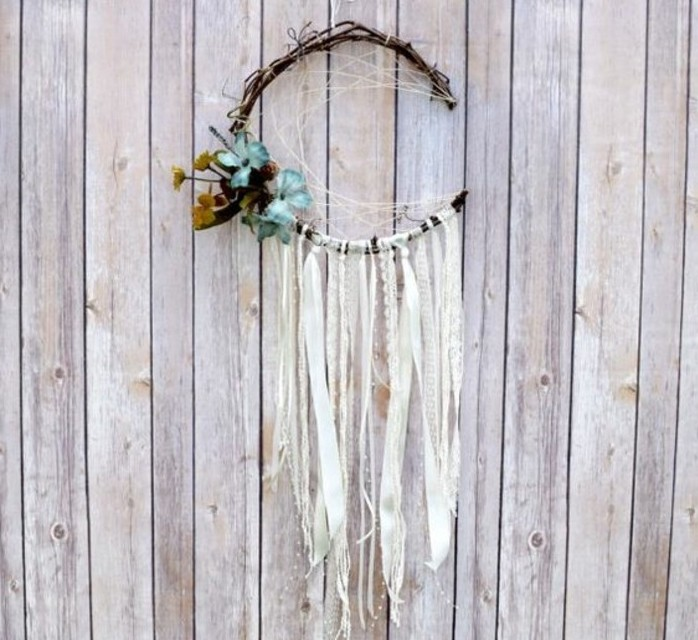 wooden fence or wall, decorated with a crescent moon dreamcatcher, pictures of dream catchers, with cream lace ribbon tassels, and pale blue flower ornaments