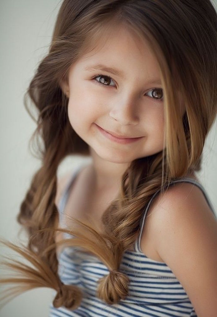 herringbone braids on smooth, long brunette hair with side part, worn by a smiling little girl, simple hairstyles, striped white and navy top