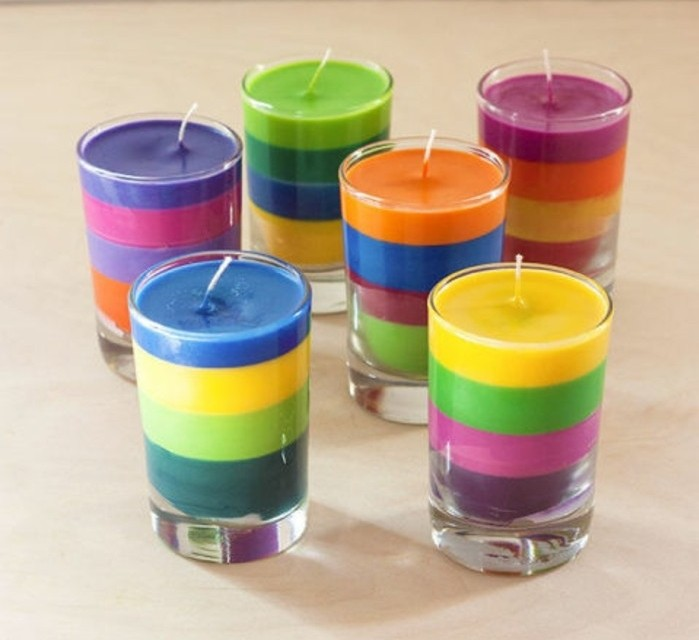layered multicolored candles, inside six clear glasses, placed on a pale beige surface, last minute birthday gifts