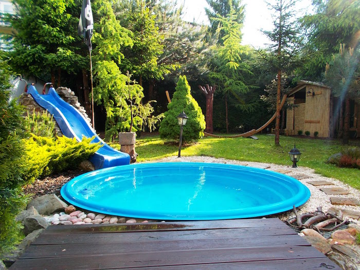 tool shed and various trees, in a garden, containing a small, round shallow pool, and a plastic slide, cool backyards, lawn with green grass and pebbles