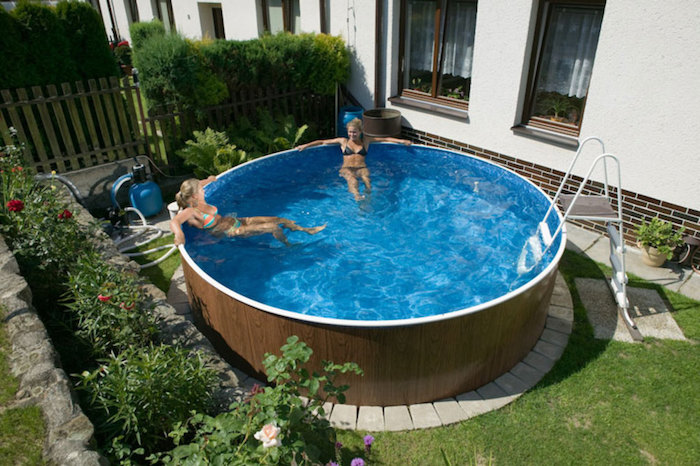 two women lounging in a tall, round pool with a white ladder, small above ground pools, in a garden next to a house