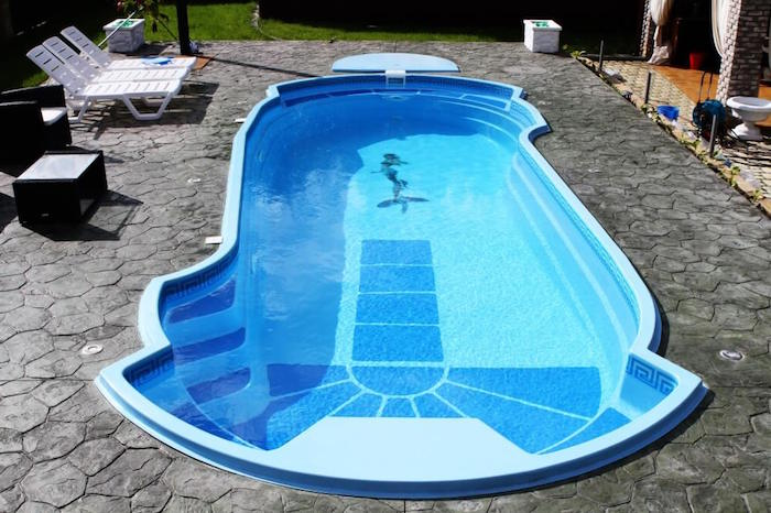 mermaid decal on the bottom of a blue pool, filled with water, and surrounded by grey stone tiles, small inground swimming pools, three white sun beds nearby