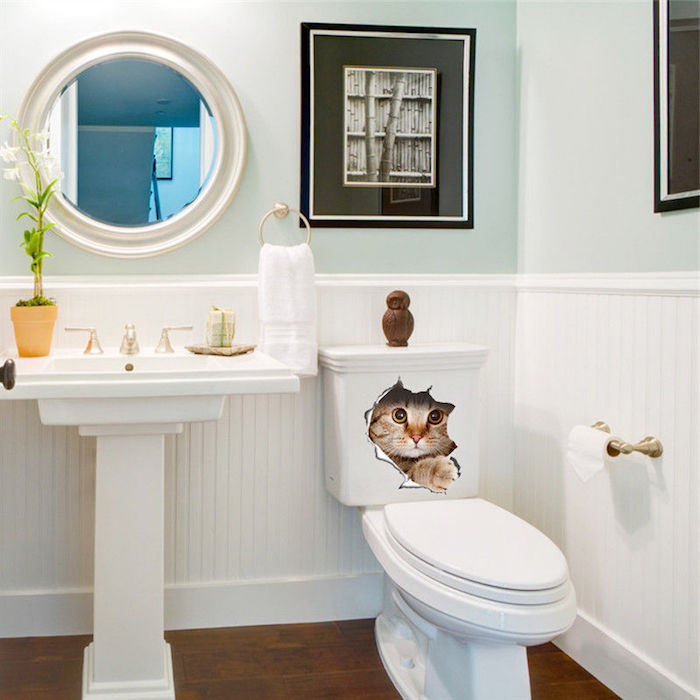 funny cat decal sticker, on a white toilet bowl, bathroom decorating ideas on a budget, room with pale duck's egg blue walls, and white panelling, containing a round mirror, and framed black and white images
