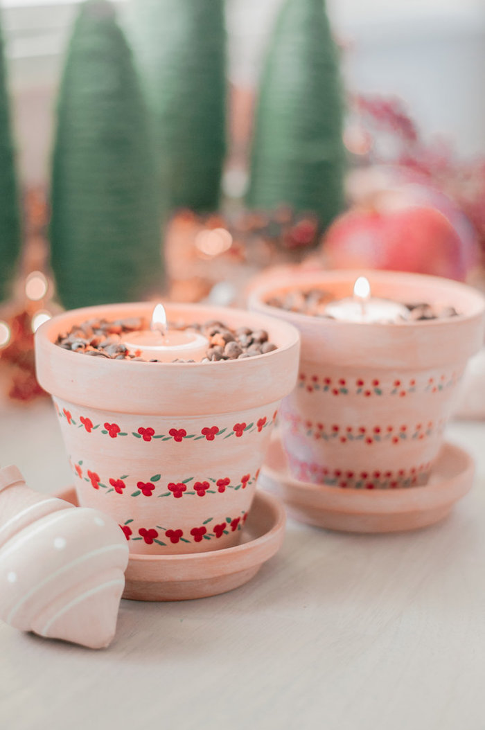 two ceramic pots, painted in pink with red flowers, best friend gifts diy, rocks and candles inside, placed on wooden table