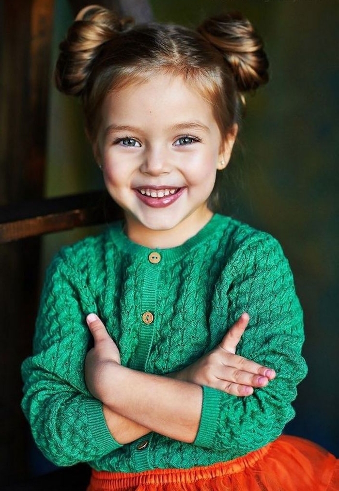 green cardigan and a red skirt, worn by a smiling, blue-eyed child, hairstyles for little girls, dark blonde hair, styled in two buns