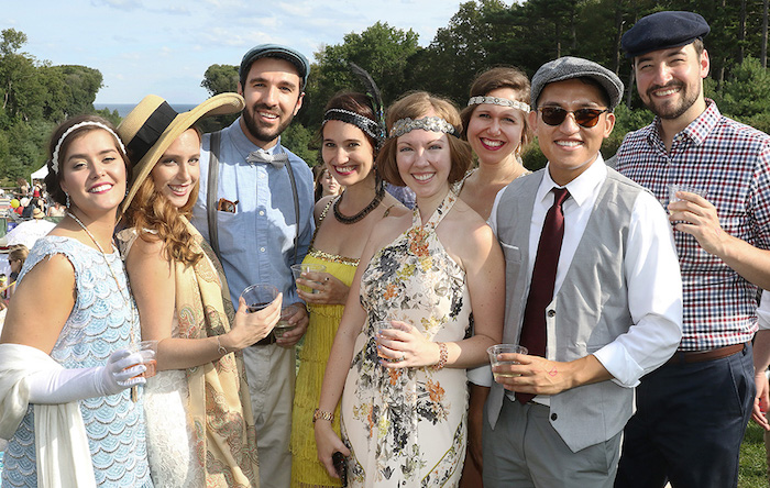 friends dressed in roaring 20s inspired outfits, smiling at the camera, and holding drinks, flapper dressed with hats and headbands, smart trousers with vests and suspenders