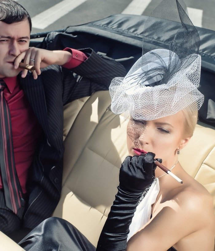 tulle hat in white and black, worn by a woman in black and white dress, smoking a cigarette, great gatsby costumes, in an antique car, next to a man smoking a cigar, what to wear to a gatsby themed party