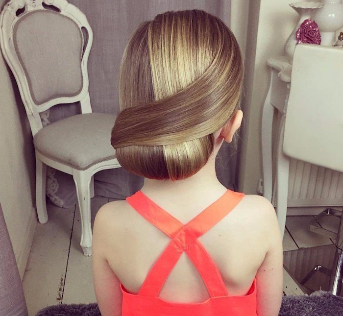 wrap-over style up-do, on blonde hair, with natural highlights, worn by a small girl, in a coral red formal dress