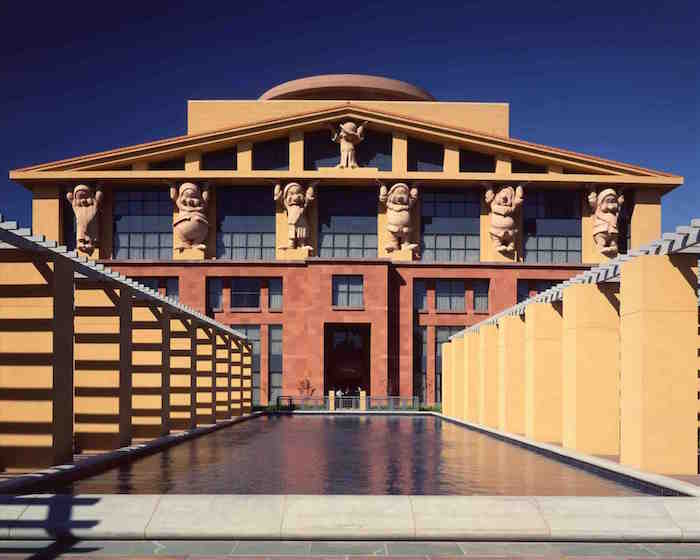 statuettes of the seven dwarves, from the animated movie snow white, propping a roof, with elements inspired by antiquity, on a yellow and orange building, disney studio's HQ in Burbank
