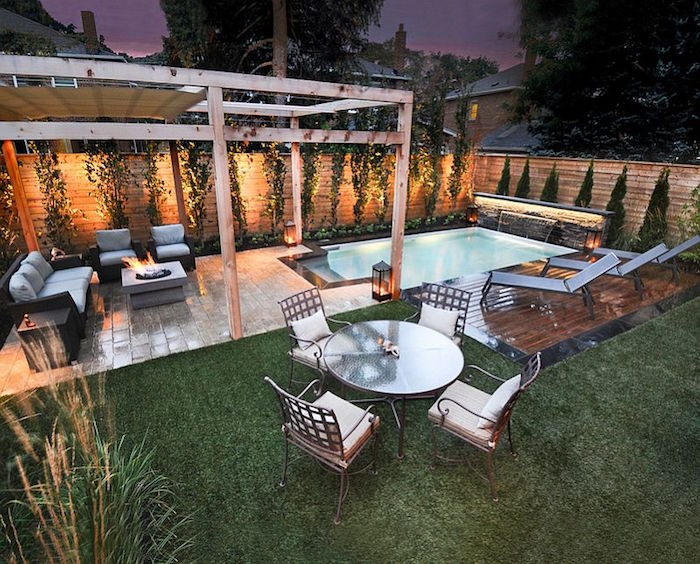 lit fire pit, near a black and grey sofa, and two matching armchairs, roman-style pool nearby, garden table with four chairs, small inground swimming pools, three sun beds