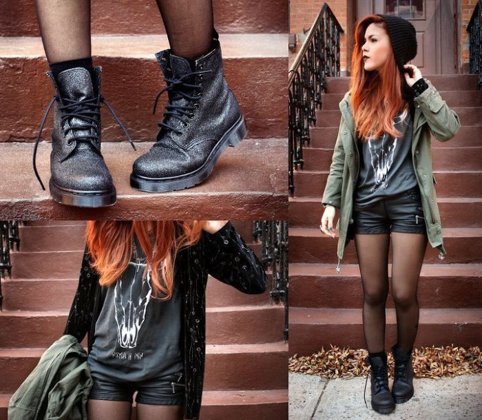 utility jacket in khaki green, worn by red-haired young woman, in black leather shorts, 90s aesthetic, sparkly black dr. marten boots, grey and white t-shirt