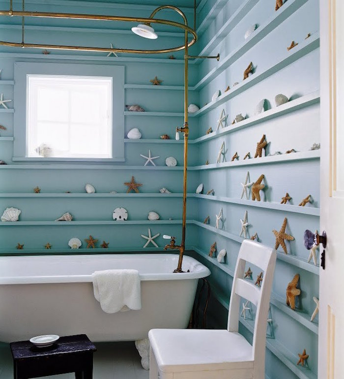 star-fish and different seashells, on shelves painted in pale turquoise, lining a wall in the same color, small bathroom décor, white bathtub and chair