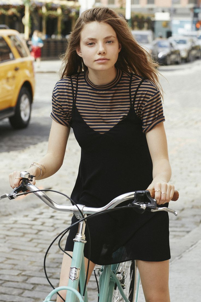 young woman with long hair, wearing a strappy black dress, over a striped cream and black t-shirt, riding a bike, 90s outfit ideas