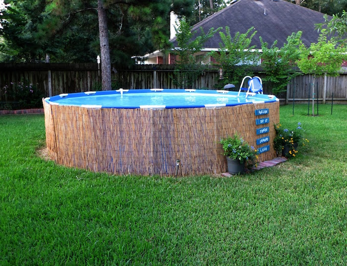 small above ground pools, straw-like material, lining a tall round pool, built on a green lawn, and decorated with two flower pots