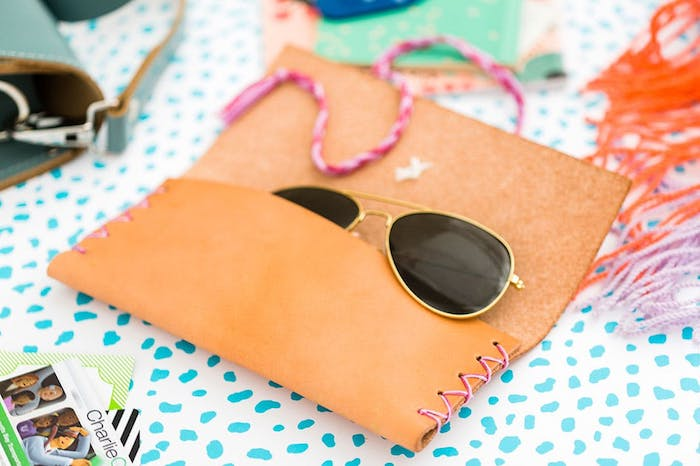leather sunglasses pouch with pink stitching, sunglasses inside, thoughtful christmas gifts, blue and white surface