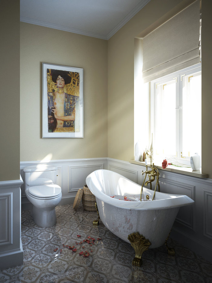 klimt artwork print, framed on the pale yellow wall, of a sunlit room, with white panelling, beige and white tiles on the floor, and a window, bathroom wall decor ideas, claw-footed antique white bathtub, and the matching toilet bowl