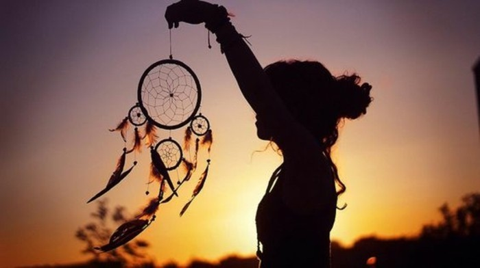diy dreamcatcher, a woman's silhouette, holding a dreamcatcher, with a yellow, orange and purple sunset in the background