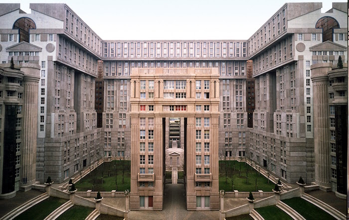 c-shaped grey building, with pale beige and off-white details, and perfectly symmetrical elements, courtyard with green grass